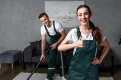 Happy young cleaning company workers using vacuum cleaner and showing. Thumb up royalty free stock photo