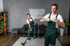 Happy young cleaning company workers using vacuum cleaner and showing. Thumbs up royalty free stock photography