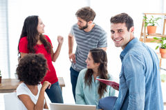 Happy young colleagues discussing in office Royalty Free Stock Image