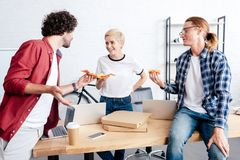 Happy young colleagues holding pizza and smiling each other. In office royalty free stock photography