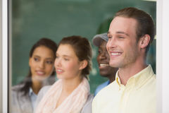 Happy young colleagues looking away in office Stock Images