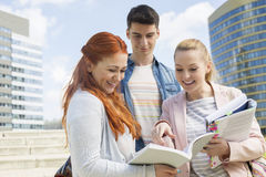 Happy young college students studying outdoors Royalty Free Stock Photos