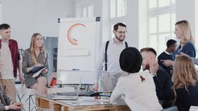 Happy young company leader businessman leading discussion with team at modern office meeting, slow motion RED EPIC. Multiethnic business colleagues listen to stock video