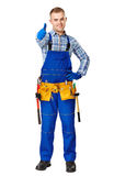 Happy young construction worker. Full length portrait of happy young male construction worker with tool belt showing thumbs up gesture isolated on white Royalty Free Stock Photography