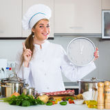 Happy young cook preparing meat ribs and checking time Stock Photo
