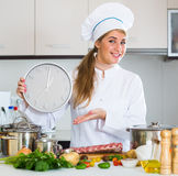 Happy young cook preparing meat ribs and checking time Royalty Free Stock Images