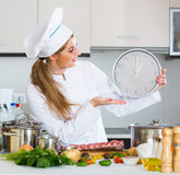 Happy young cook preparing meat ribs and checking time Stock Images
