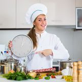 Happy young cook preparing meat ribs and checking time Royalty Free Stock Photography