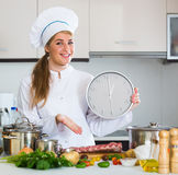 Happy young cook preparing meat ribs and checking time Stock Image