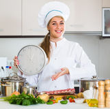 Happy young cook preparing meat ribs and checking time Royalty Free Stock Photos