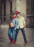 Happy young cool latin couple together outdoors with pregnant woman showing belly stock photos