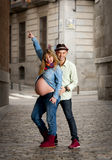 Happy young cool  latin couple together outdoors with pregnant woman showing belly. Happy young cool  latin couple together outdoors with pregnant women showing Stock Photo