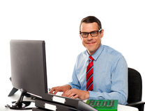 Happy young corporate man using computer Stock Photos