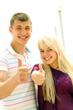 Happy young couple. Young couple outdoors with thumbs up royalty free stock photo