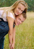 Happy young couple. Happy man giving piggyback ride to woman outdoors Stock Photos
