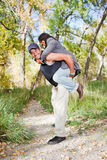 Happy young couple. Happy young guy with his girlfriend on piggyback. Shallow DOF, guy's face is the focus point Stock Images