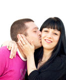 Happy Young couple. Portrait of a beautiful young couple hugging.Male kissing his girlfriend  against white background Stock Photos