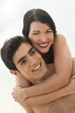 Happy young couple. A happy young couple together with the womans arms around the man Stock Images