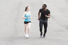 Happy young couple afro-american man and european woman running together. A loving couple is run, engaged in sports royalty free stock photography