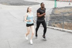 Happy young couple afro-american man and european woman running together. A loving couple is run, engaged in sports stock photography