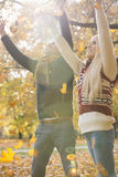 Happy young couple with arms raised enjoying falling autumn leaves in park royalty free stock photos