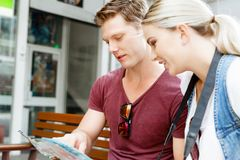 New places to explore. Happy young couple as tourists with a map Stock Images