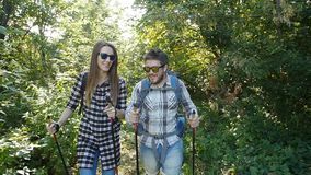 Young couple with backpacks in the forest. Travel and Hiking Concept. Happy Young couple with backpacks in the forest. Travel and Hiking Concept stock video footage