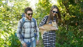 Young couple with their cat with backpacks in the forest. Travel and Hiking Concept. Happy Young couple with backpacks in the forest. Travel and Hiking Concept stock video