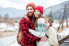 Happy young couple with backpacks hugging in mountains Stock Image