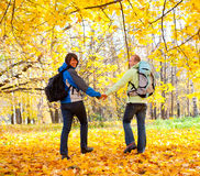 Happy young couple with backpacks in the park. Fall Stock Image