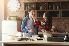 Happy young couple baking in loft kitchen. Happy young women and men baking pie and having fun in loft kitchen. Young family cooking at home, using digital stock image