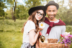 Happy young couple with basket of drinks, food and flowers. Portrait of happy young couple with basket of drinks, food and flowers standing outdoors stock photo