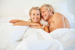 Happy young couple in bed stock images