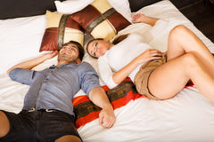 Happy young couple on the bed in a hotel room Royalty Free Stock Photos