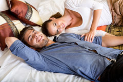 Happy young couple on the bed in a hotel room Royalty Free Stock Image