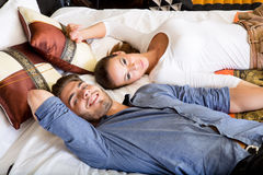 Happy young couple on the bed in a hotel room Royalty Free Stock Images