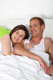 Happy young couple in bed Stock Photography