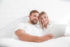 Sensual young couple together in bed. Happy couple in bedroom  on a white background. Happy young couple on the bed watching film on tablet and smiling Royalty Free Stock Image