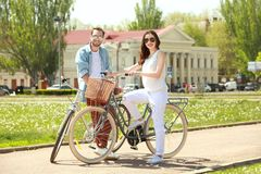 Happy young couple with bicycles in park. On sunny day Royalty Free Stock Image