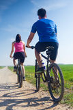 Happy young  couple on a bike ride in the countryside Royalty Free Stock Photography