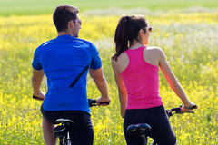 Happy young  couple on a bike ride in the countryside Stock Photos