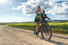 Happy young  couple on a bike ride in the countryside Royalty Free Stock Images