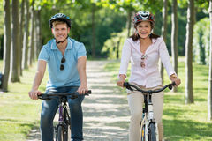 Happy Young Couple Biking In Park Royalty Free Stock Image
