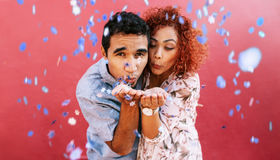 Happy young couple blowing confetti in celebration of their love stock image