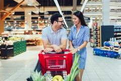 Young couple bonding to each other and smiling while walking while walking in food store with shopping cart stock image