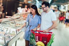Young couple bonding to each other and smiling while walking while walking in food store with shopping cart stock photo