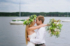 Happy young couple with a bouquet and a wreath embracing and kissing Royalty Free Stock Images