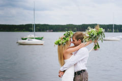 Happy young couple with a bouquet and a wreath embracing and kissing Royalty Free Stock Image