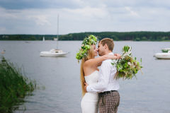 Happy young couple with a bouquet and a wreath embracing and kissing Royalty Free Stock Photography