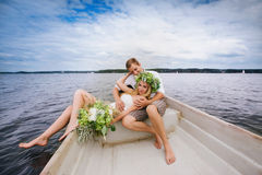 Happy young couple with a bouquet and a wreath embracing and kissing Stock Photo